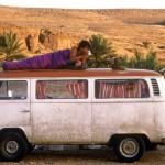 Hippie-Van-Mann-in-Schlafsack-auf-Dach